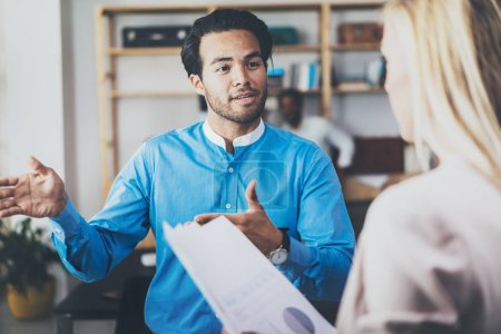 Two coworkers discussing business strategy in modern office.Successful confident hispanic businessman talking with woman. Horizontal, blurred background.