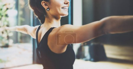 Photo for Close up view of gorgeous young woman practicing yoga indoor. Beautiful girl practice Warrior Light asana.Calmness and relax, female happiness concept.Horizontal, blurred background - Royalty Free Image