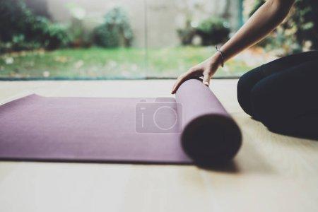 Photo pour Bouchent la vue du superbe jeune femme pratique l'yoga intérieur. Belle jeune fille préparant nattes pour classe de pratique. Calme et détente, le concept de bonheur féminin. Horizontal, flou fond - image libre de droit