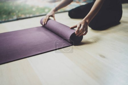 Close up view of female hands.Gorgeous young woman practicing yoga indoor. Beautiful girl preparing mats for practice class.Calmness and relax, happiness concept.Horizontal, blurred background.