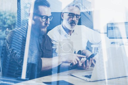 Double exposure concept.Team of business people making great work discussion in studio.Young bearded man showing mobile to adult businessman.Skyscraper office building blurred background.Horizontal.