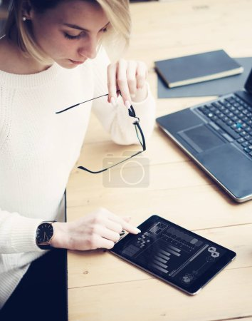 Female hand touching tablet