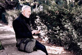 Pensive middle age businessman touching smartphone display while resting in a city park at sunny day.Horizontal,blurred background, film effect.