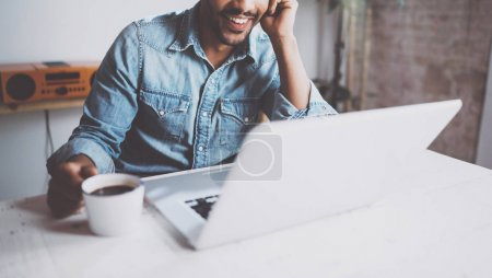 Happy bearded African man making video conversation via modern laptop with partners while holding white cup black coffee at home.Concept of young business people.Blurred background,crop.