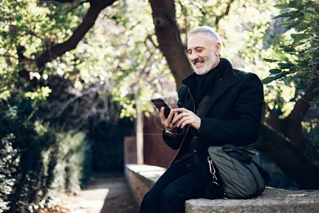 Smiling middle age businessman using smartphone while resting in a city park.Horizontal,blurred background, film effect.