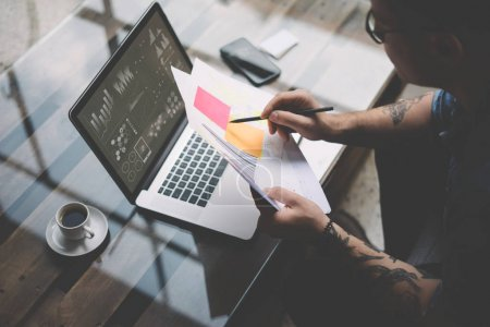 Photo for Young tattooed coworker working with laptop at office.Businessman analyze documents on hands.Graphs,online interfaces,diagram on notebook screen.Horizontal, blurred, top view - Royalty Free Image