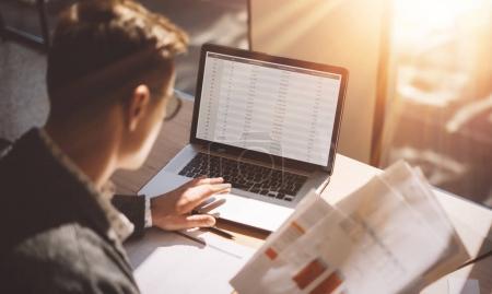 Photo pour Jeune analyste de finances bancaires en lunettes travaillant au bureau ensoleillé sur ordinateur portable tout en étant assis à une table en bois. Homme d'affaires analyser l'actualité boursière sur l'écran de l'ordinateur portable. Arrière-plan flou, horizontale - image libre de droit