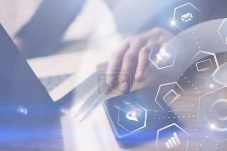 Photo for Concept of virtual screen,connections icon and digital interfaces.Closeup view of Businessman working at office on laptop.Man pointing hand on thouch screen of smartphone.Blurred background - Royalty Free Image