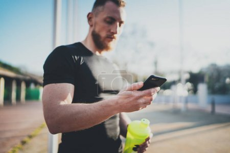 Muscular handsome athlete checking sport results on smartphone application and smart watch after good workout session on city park in the sunny morning.Blurred background.