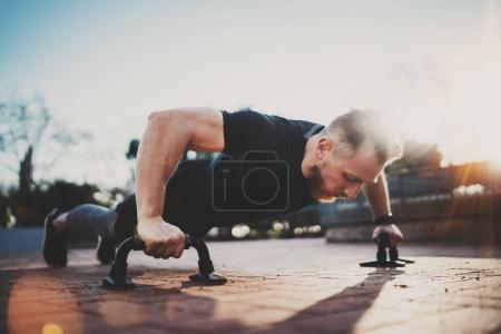 Photo for Handsome young sport man doing pushups in the park on the sunny morning.Healthy lifestyle concept.Training outdoors.Blurred background - Royalty Free Image