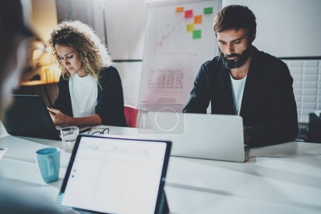 Photo for Group of young coworkers working together on laptops at modern coworking studio.Horizontal mockup.Blurred background - Royalty Free Image