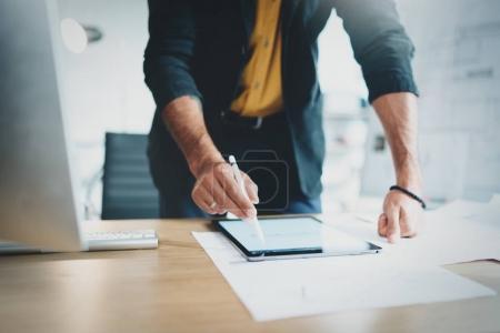Foto de Vista de cerca del hombre en ropa formal que trabaja con la computadora portátil de la tableta y dibujos planos digitales en la oficina luminosa moderna.Horizontal.Blurred fondo - Imagen libre de derechos