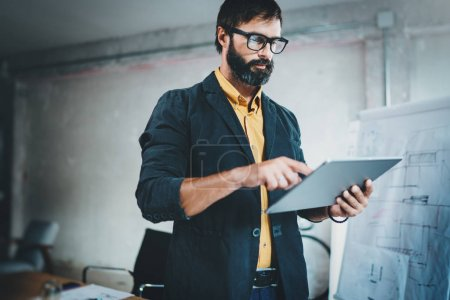 Bearded young coworker working at lightful office.Man using contemporary mobile digital tablet.Horizontal.Blurred background.