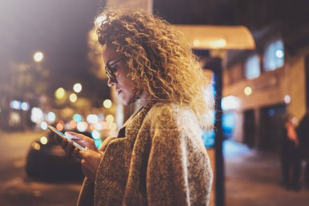 Beautiful girl hipster wearing glasses holding smart phone hands, during night walking in european vocation. Bokeh and flares effects on blurred background.