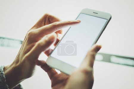 Girl pointing finger on screen smartphone.Female hands texting message mobile phone.Closeup on blurred light coloured background.