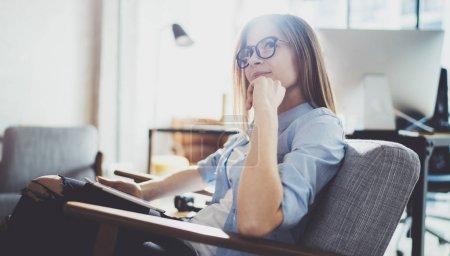 Photo pour Belle jeune blonde portant des lunettes et utilisant une tablette électronique tactile sur un lieu de travail ensoleillé. Fond flou - image libre de droit
