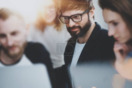 Group of young entrepreneurs are looking for a business solution during working time at sunny office.Business people meeting concept.Blurred background.Horizontal.Flares.