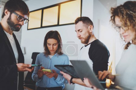 Business meeting concept.Coworkers team working with mobile devices at modern office.Blurred background.Horizontal.