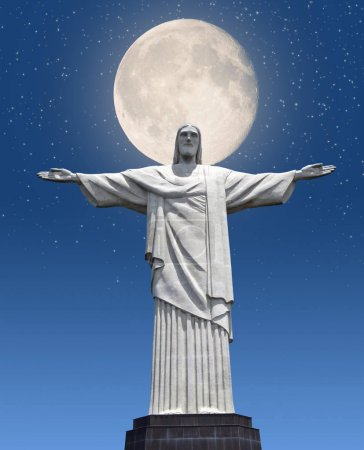 Bottom view of Jesus Christ monument with rising hands on dark blue sky with giant full moon and stars background.