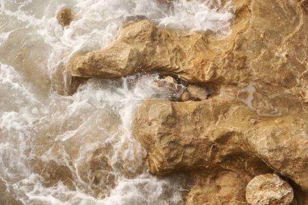 Photo pour Un gros plan sur l'eau turquoise de la mer Méditerranée et de puissantes vagues battant contre les rochers de la côte. focus sélectif . - image libre de droit