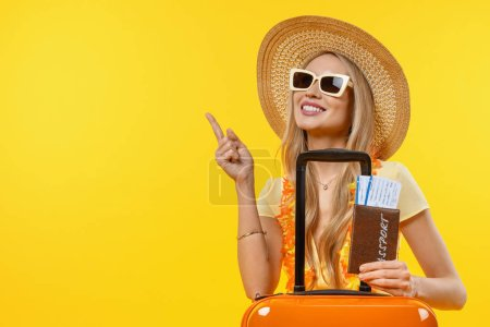 Photo for Young smiling woman pointing in vacation with suitcase and passport over isolated yellow background - Royalty Free Image