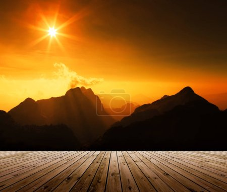 Wooden plank with beautiful landscape sunrise above mountain.