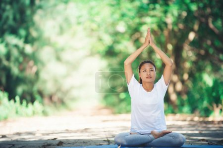Young asian woman doing yoga in the morning at the...