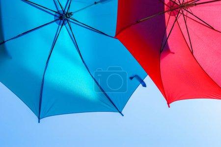 Deux parapluies colorés en arrière-plan d'un ciel clair et ensoleillé. Parapluies bleus et rouges en expansion. Décoration de rue. Espace pour le texte .