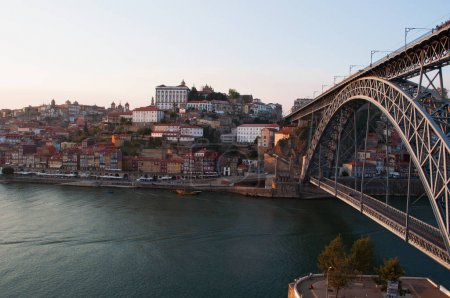 Portugal: boats at sunset and the skyline of Porto with view of the Luiz I, the double-decked metal arch bridge on the Douro River between Porto and Vila Nova de Gaia