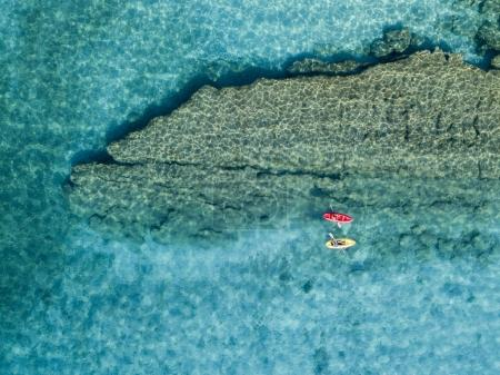 Aerial view of a canoe in the water floating on a transparent sea. Bathers at sea. Zambrone, Calabria, Italy. Diving relaxation and summer vacations. Italian coasts, beaches and rocks