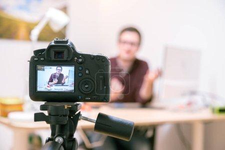 Photo pour Caméra sur un trépied filmant un blogueur à la maison assis sur son espace de travail - image libre de droit