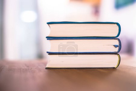 Photo for Stack of books lying on wooden desk at home. Knowledge and science - Royalty Free Image