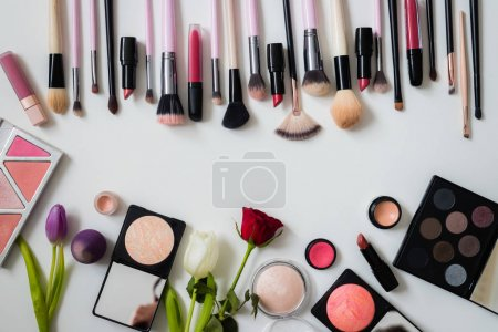 Photo for Set of makeup brushes and other accessories. Lipstick, mascara, nail polish, eyeshadow, powder, eyelash and foundation. Products for makeup on white background, top view. - Royalty Free Image
