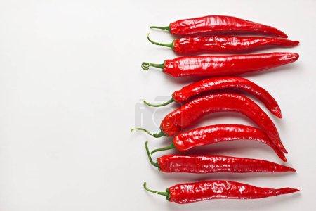 Photo pour Piments chili rouges sur table blanche en bois. Ingrédient alimentaire épicé chaud - image libre de droit