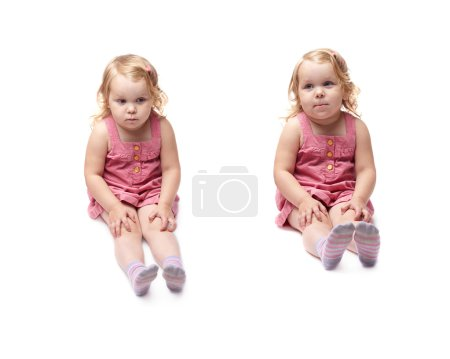 Young little girl sitting over isolated white background