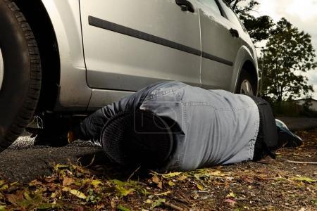 Photo pour Assassin s installation explosif plastique sous la voiture en plein air sur la place de parking - image libre de droit