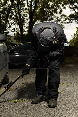 Le policier vérifie la voiture pour un éventuel engin explosif