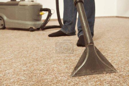 Photo pour Homme caucasien nettoyer profondément tapis avec machine de nettoyage humide - image libre de droit