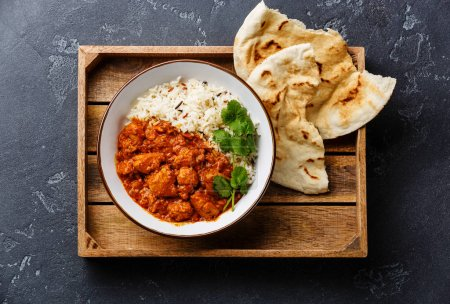 Photo for Chicken tikka masala spicy curry meat food with rice and fresh naan bread in wooden tray on black stone background - Royalty Free Image