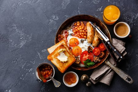 Photo for English Breakfast in cooking pan with fried eggs, sausages, bacon, beans, toasts and coffee on dark stone background - Royalty Free Image