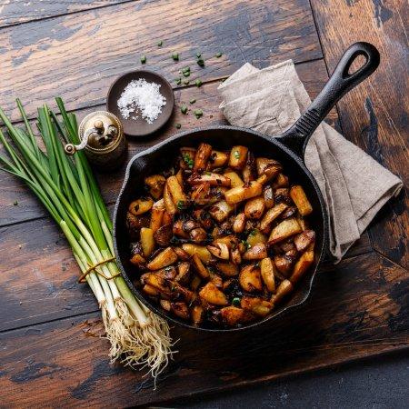 Photo pour Pommes de terre rôties aux cèpes dans pan sur fond en bois de cuisine - image libre de droit