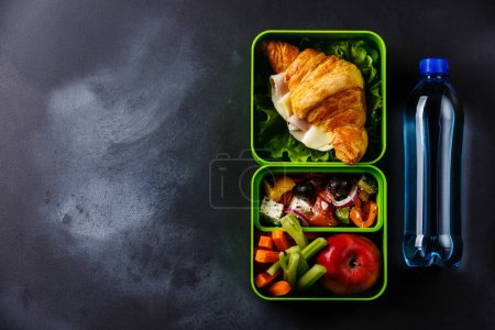 Photo for Take out food Lunch box with Croissant sandwich, Greek salad and vegetables with bottle of water on blackboard background - Royalty Free Image