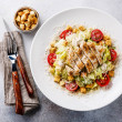 Caesar salad with chicken breast on gray backgroun...