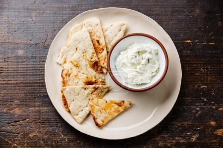 Photo for Yogurt dip with herbs Dzadziki cacik sauce and Pita bread on wooden background - Royalty Free Image