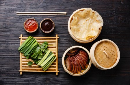 Sliced Peking Duck in bamboo steamer served with fresh cucumber, green onions, cilantro and roasted wheaten chinese pancakes with sauce Hoysin on black background