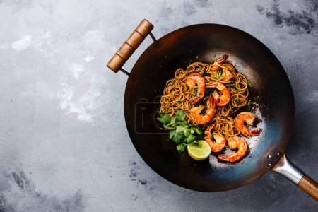 Ramen stir-fry noodles with shrimp in wok pan on gray concrete background