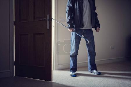 Photo pour Cambrioleur commettant un cambriolage dans une maison avec un pied-de-biche - image libre de droit