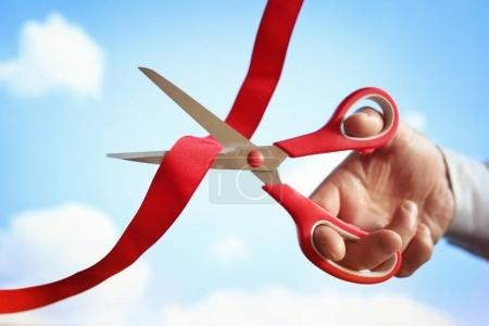Cutting red ribbon with scissors