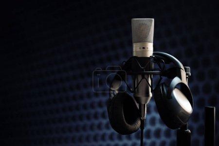 Studio microphone and headphones on mic stand agai...