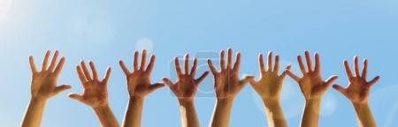 Photo for Raised hands on a blue sky background with copy space - Royalty Free Image